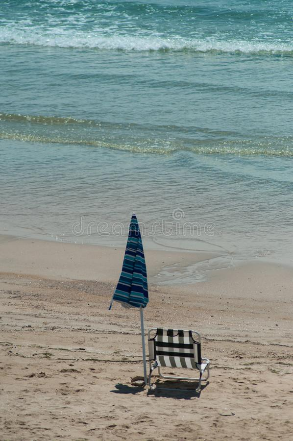 Chair and umbrella on the beach. Closeup of chair and umbrella on the beach stock photos