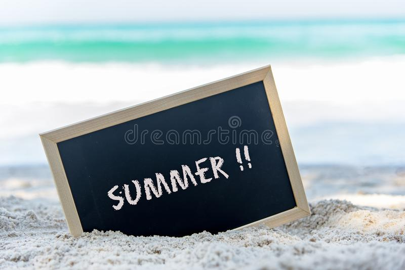 Closeup of a chalkboard with the text summer written on the sand of a beach. royalty free stock photo