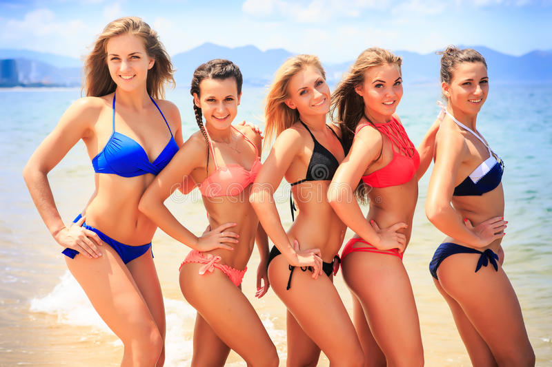 Closeup cheerleaders in bikinis stand closely in line on beach royalty free stock image