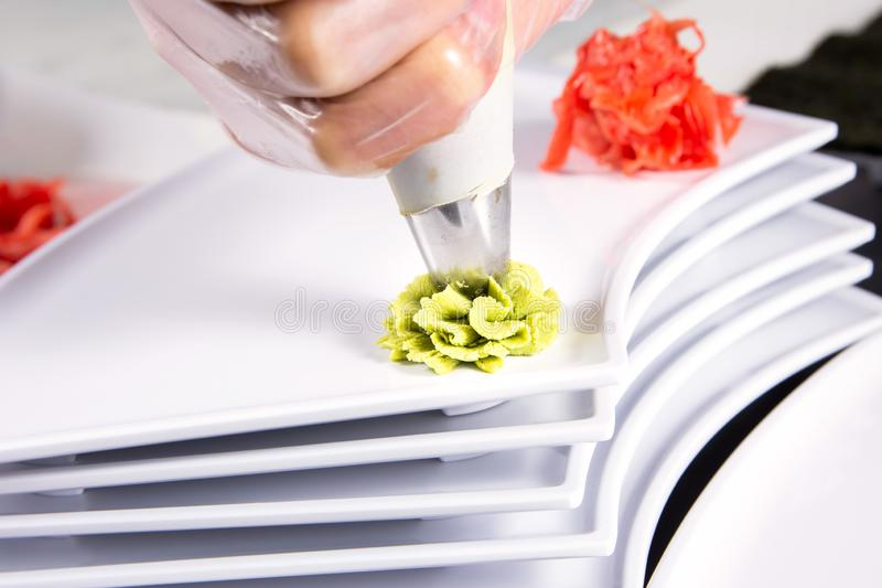 Closeup of chef hands rolling up sushi setting on plate on kitchen royalty free stock photography