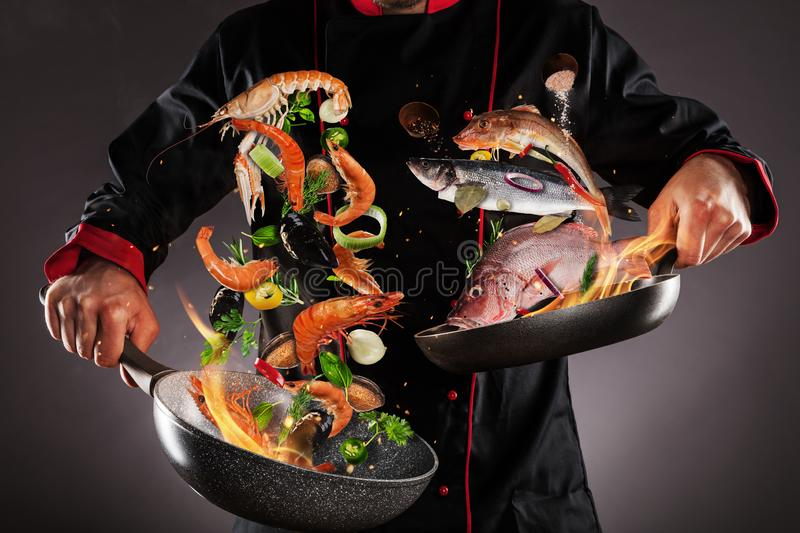 Closeup of chef throwing sea fruit and fish. Into the air, fire flames around. Concept of food preparation royalty free stock photo