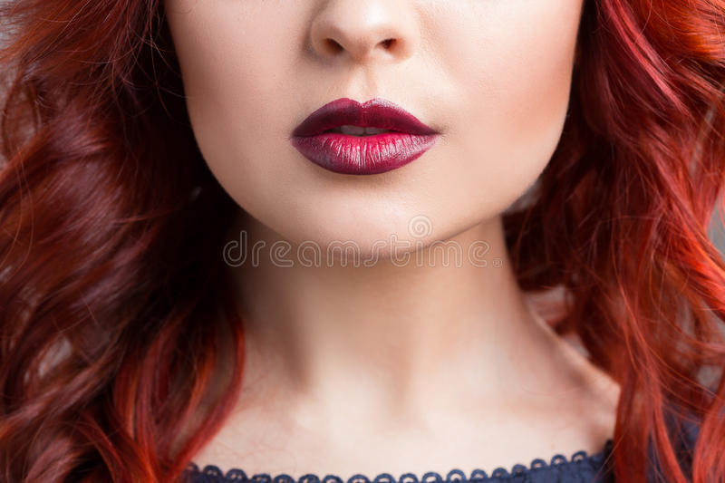 Closeup cherry lips. girl with red hair. the lower. Part of the face stock images