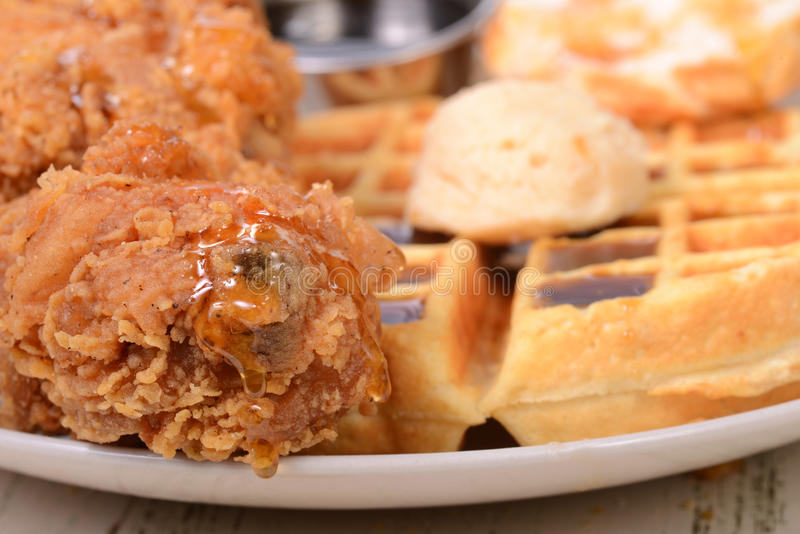 Closeup of Chicken and Waffles. With honey, maple butter and maple syrup royalty free stock photos