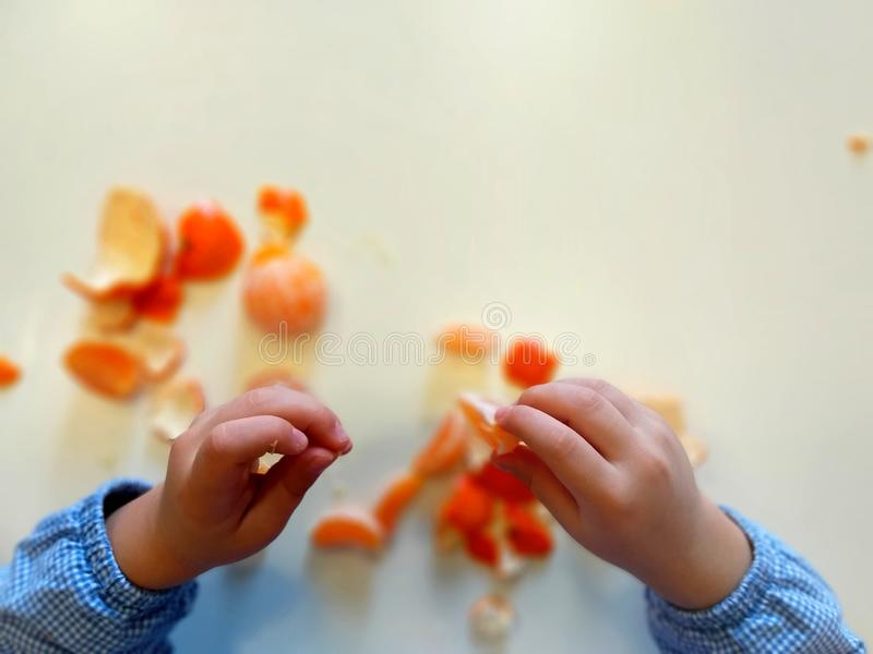Closeup of child hands peeling fruit wearing school uniform - learning by doing, education, kindergarten, snack time concept stock photos