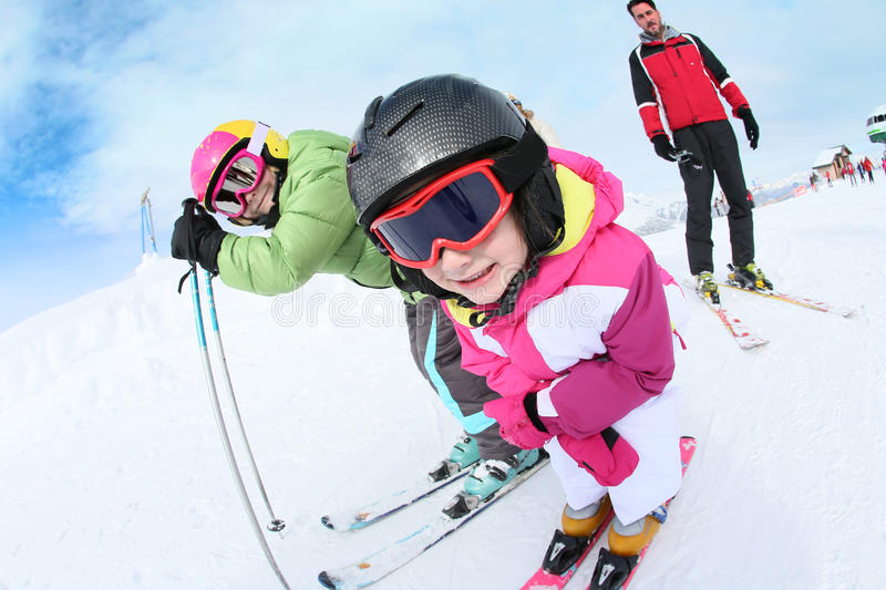 Closeup of children learning how to ski. Young girl learning how to ski with family stock photo