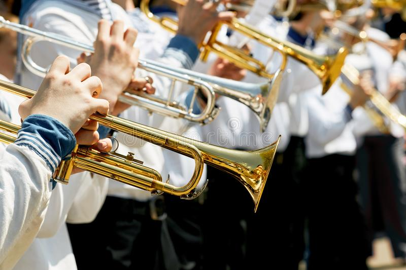 Closeup of children`s brass band. Children play on golden pipes. The concept of lifestyle and youth culture royalty free stock photos
