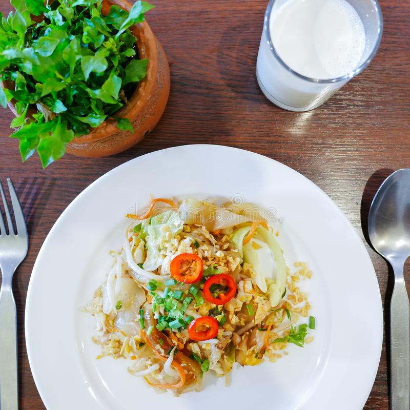 Closeup of chinese food, Fried noodle mixed with egg and vegetables on white plate royalty free stock photo