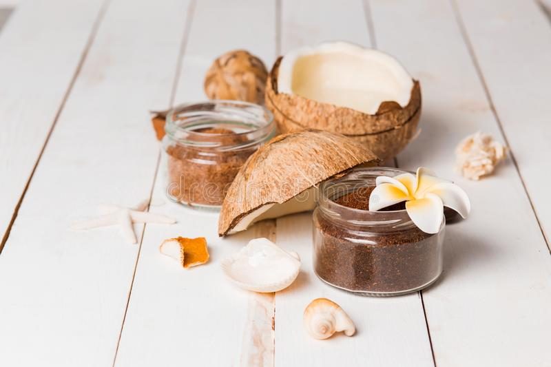 Closeup of chocolate coconut scrub for face and body in small jars with shells and a flower on a white wooden background royalty free stock image