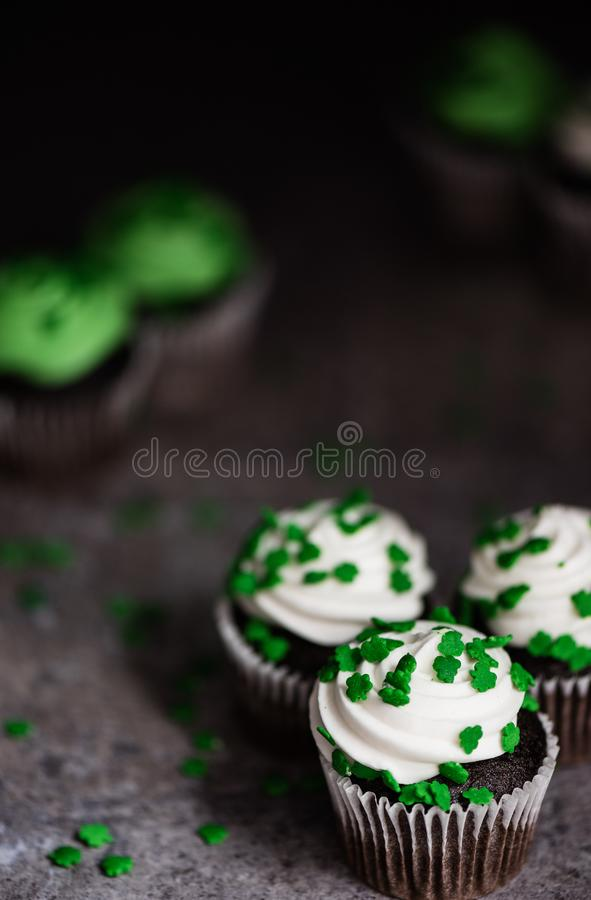 Closeup of chocolate cupcakes with white frosting and green sham royalty free stock photography