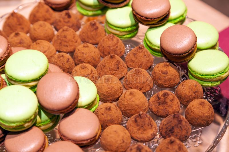 Closeup chocolate and pistachio macaroons and truffles sprinkled with cocoa in a crystal plate. View from above. Concept table stock image
