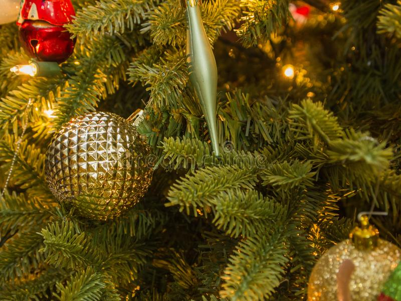 Closeup of Christmas decorations with gold ball and green icicle. Closeup of Christmas decorations with gold ball and green icicle in foreground stock image