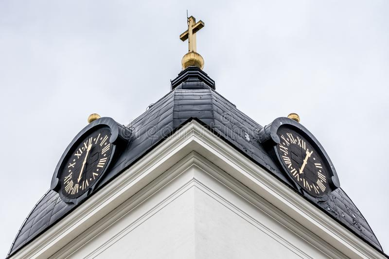 Closeup of a church clock tower in Husby. Closeup of a white church tower in Husby Sweden with dual black clock dials with gold colored numbers and pointers royalty free stock photography