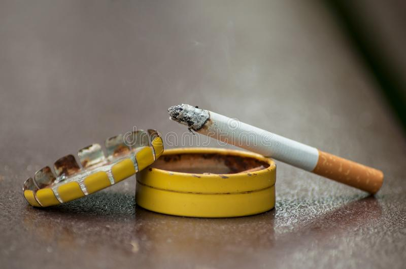 Cigarette on metallic pocket ashtray on wooden table. Closeup of cigarette on metallic pocket ashtray on wooden table background royalty free stock photo