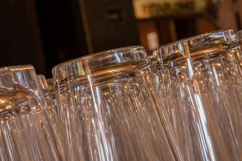 Closeup of shiny pint glasses in a row tipping from right to left stock photos