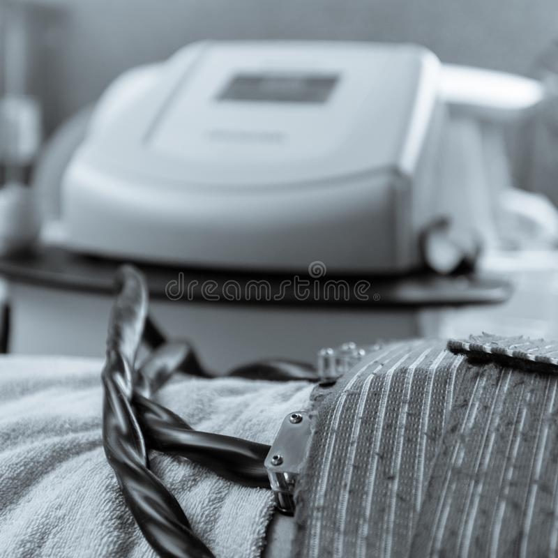 Cryolipolysis fat treatment. Closeup of client getting cryolipolysis fat treatment procedure in beauty salon black white image with a blue toning stock images
