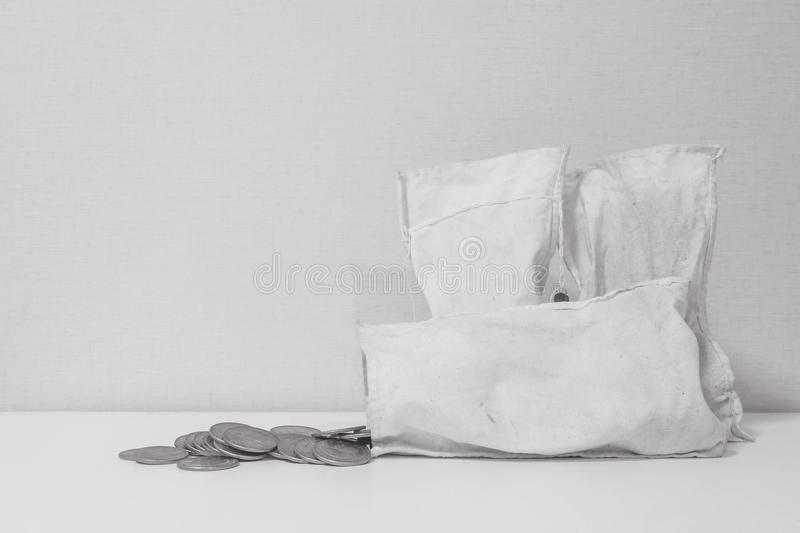 Closeup coin with old white money bag on the table and wallpaper in room textured background in black and white tone with copy spa royalty free stock photo
