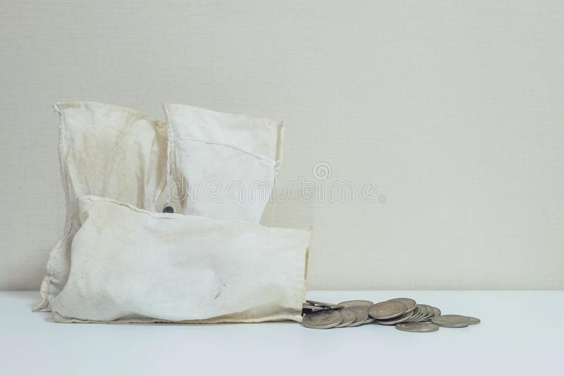 Closeup coin with old white money bag on the table and wallpaper in room textured background with copy space stock images
