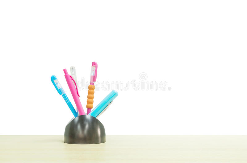 Closeup color pen with black ceramic desk tidy for pen on blurred wooden desk isolated on white background. Color pen with black ceramic desk tidy for pen on stock image