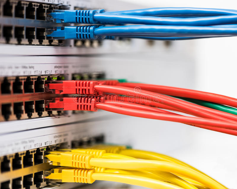 Closeup of colored computer network cables connected to a swi stock photo