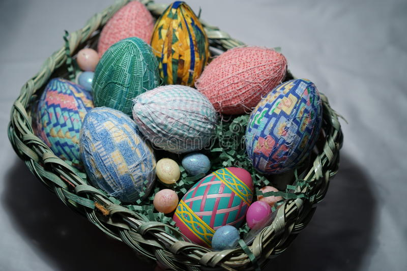 Closeup of colorful handmade Easter eggs. Colorful cloth-wrapped Easter eggs are nestled on shredded paper grass in green Easter basket stock photography