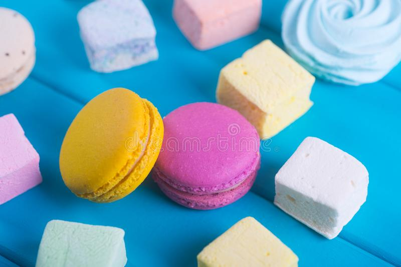 Closeup colorful macaroons and different marshmallow on on vibrant blue background. stock photos