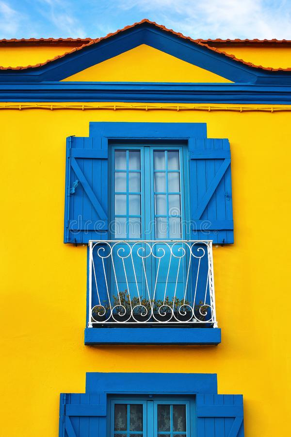 Closeup of colorful Portuguese yellow house facade with old blue windows and wooden shutters in Portugal town, Europe. Travel and architecture concept royalty free stock photos