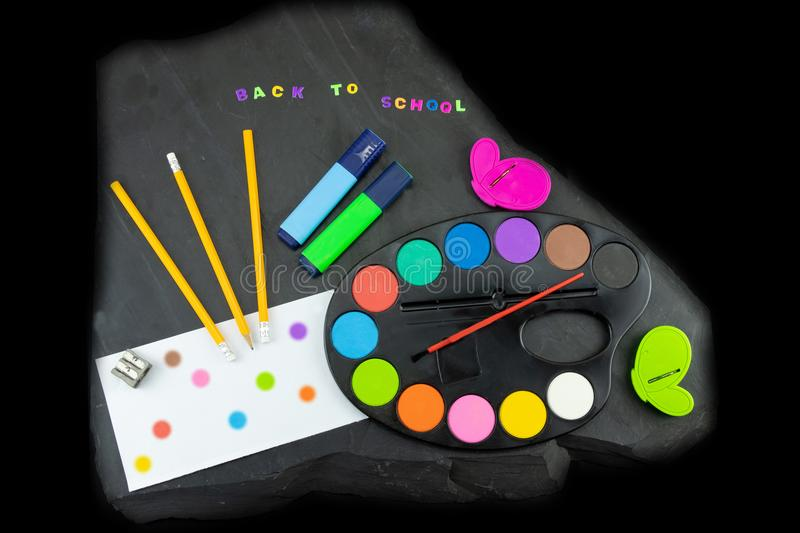 Closeup of colorful school supplies with copy space on blackboard background. Back to school written with colorful letters on stock photo