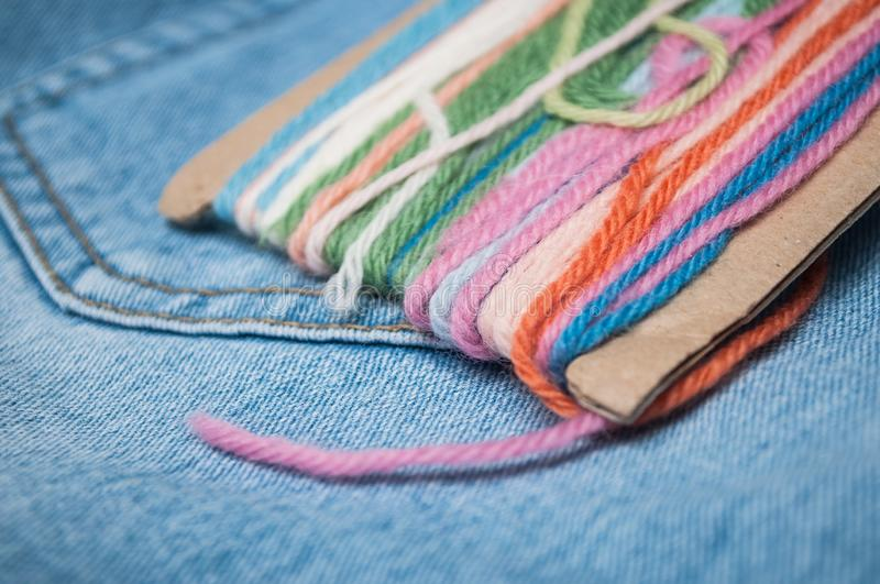 Colorful woolen threads on blue jeans background. Closeup of colorful woolen threads on blue jeans background stock photography