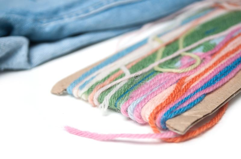 Colorful woolen threads on white table on blue jeans background. Closeup of colorful woolen threads on white table on blue jeans background royalty free stock photography