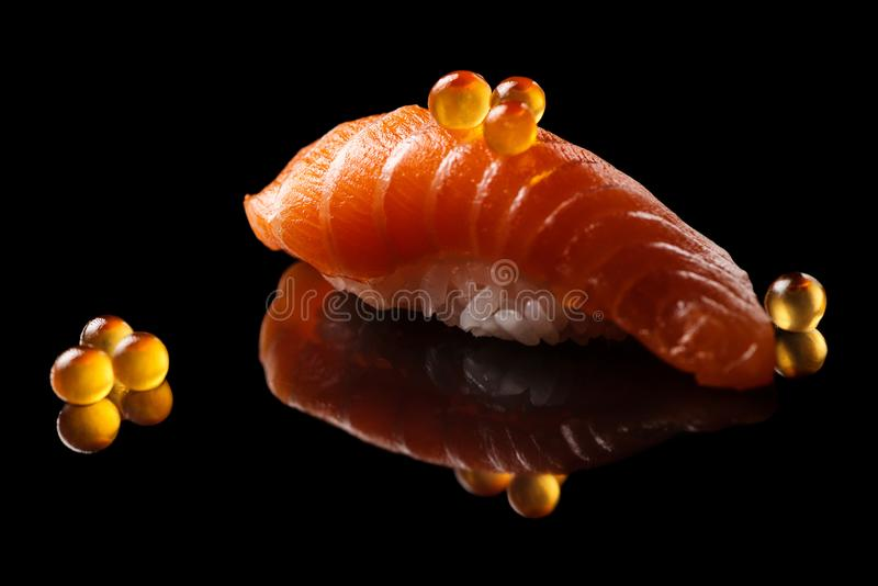 Closeup composition of fresh salmon sashimi sushi with caviar. Isolated on a dark background royalty free stock photos
