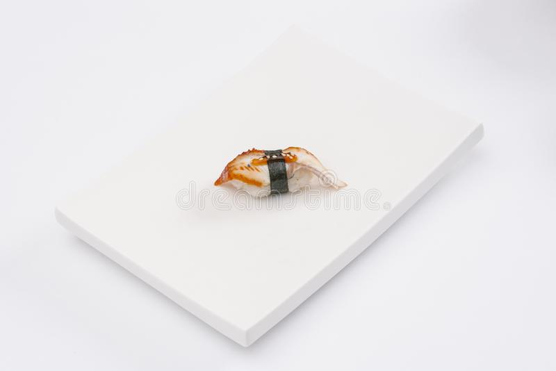 Closeup composition of one fresh salmon sashimi sushi with caviar on top on white plate. White background. Top view. CLose up stock photography