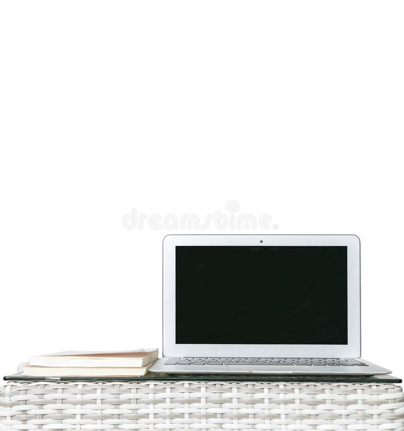 Closeup computer on blurred wood weave table and book isolated on white background , beautiful work place interior of house. Closeup computer on wood weave table stock photos
