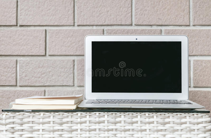 Closeup computer on blurred wood weave table and brown brick wall texture background , beautiful work place interior of house stock photo