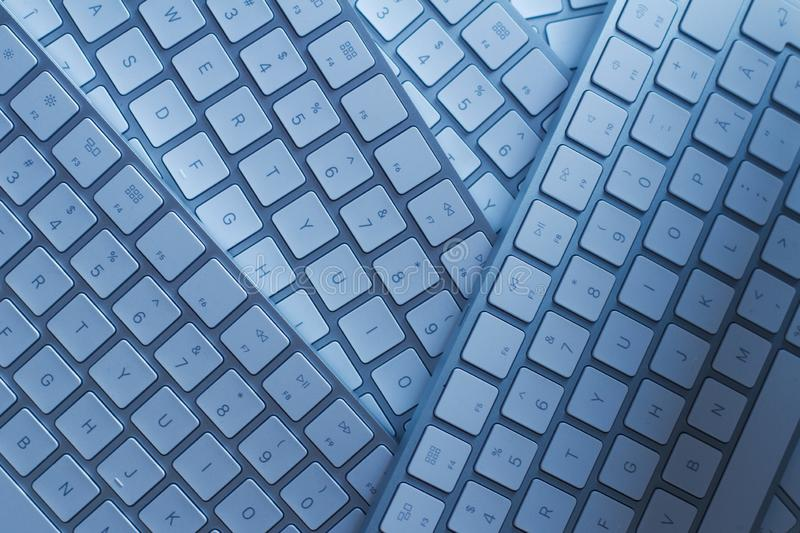 Closeup of computer keyboards on a black dark desk. Top view macro closeup of many white wireless aluminum computer keyboards on top of each other on a dark royalty free stock images