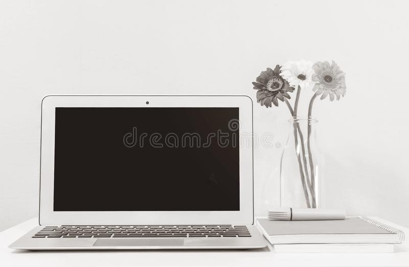 Closeup computer notebook on blurred white wood desk and wallpaper wall in room texture background , beautiful work place interior stock illustration