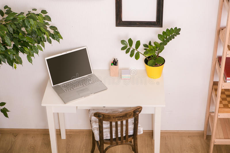 Closeup of computer on table at home or office. Closeup picture of laptop computer represented on white table with flower pot on at home or office. Business at royalty free stock images
