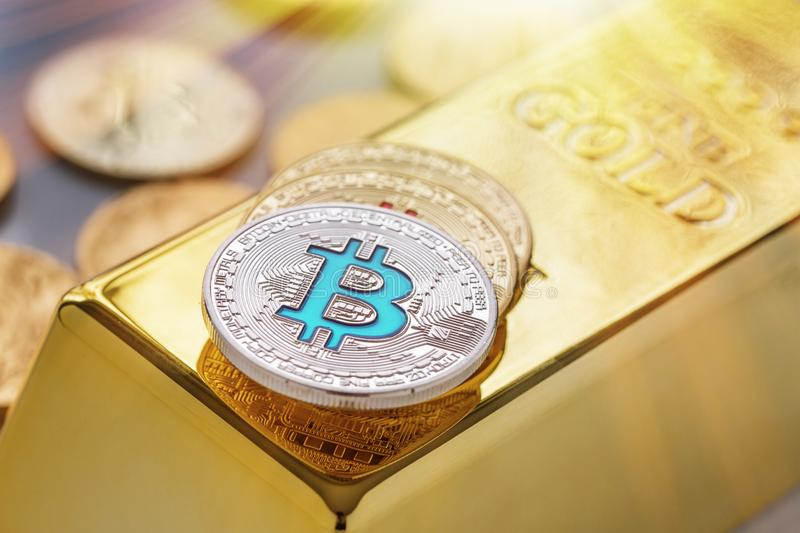 Concept of Cryptocurrency physical bitcoin with gold bar and sunburst effect royalty free stock images
