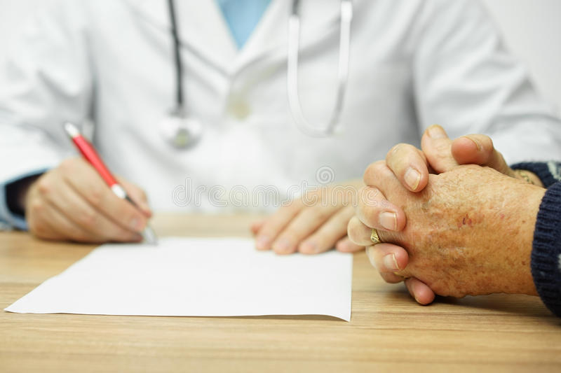 Closeup of concerned very old woman hands while doctor writing d royalty free stock photo