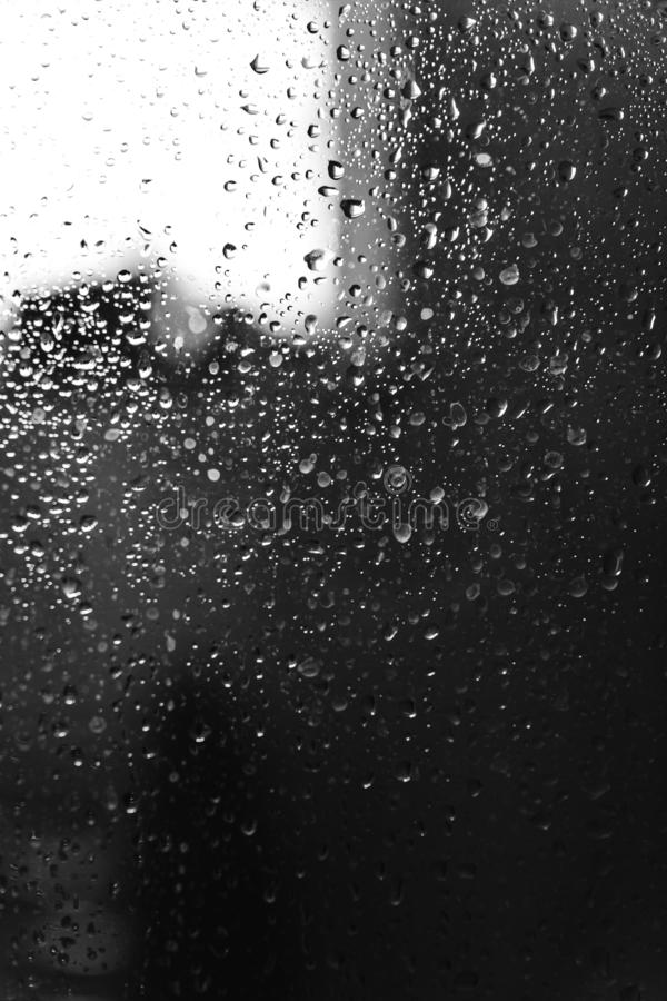 Closeup of condensation patterns on glass window, water droplets with light reflection and refraction, black and white royalty free stock photography