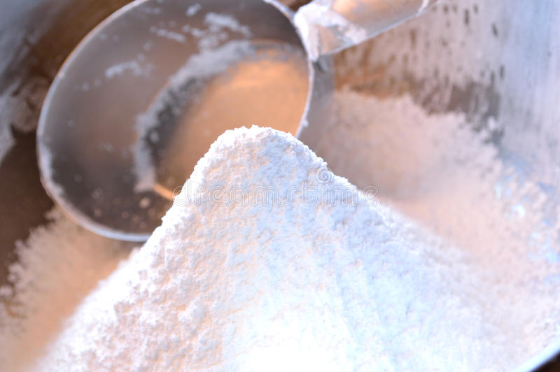 Closeup of confectioner's sugar in bowl with measuring cup royalty free stock photo