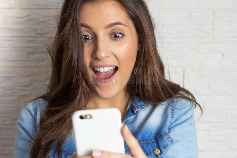 Closeup woman reading good news on mobile phone. Open mouth and big smile. E-commerce, online shopping, stock images