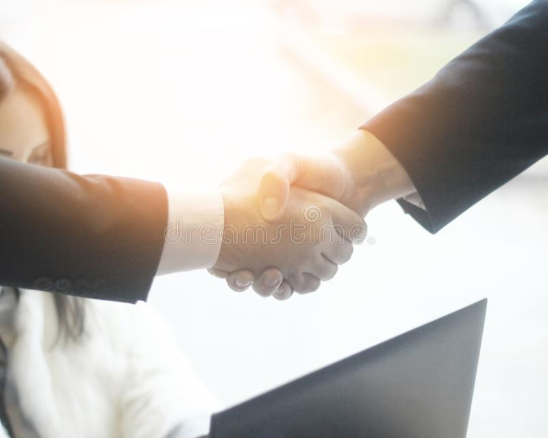 Confident handshake of business partners on background of office stock image