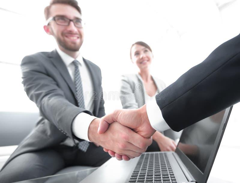 Closeup. confident handshake colleagues in officce. Closeup. confident handshake colleagues in front of an open laptop Desk stock photos