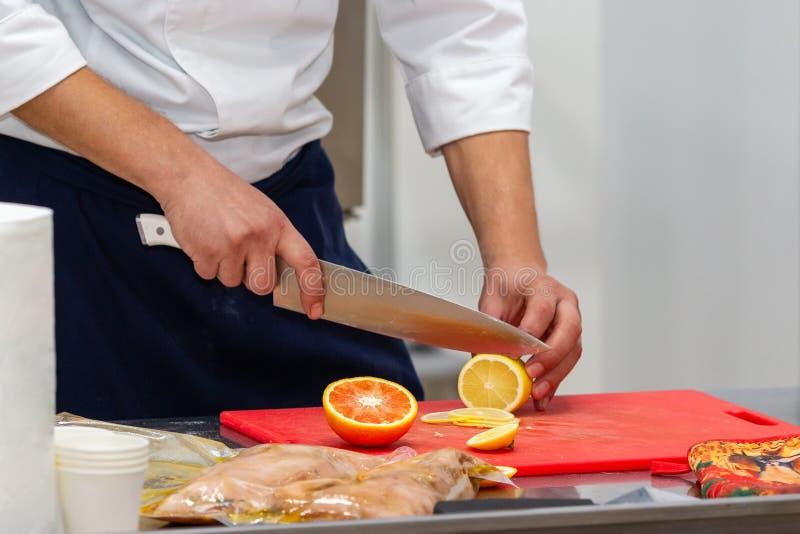 Closeup of a cook cutting lemon stock images