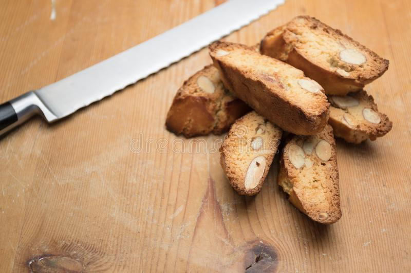 Tozzetti / Cantucci. Closeup of cooked Italian tozzetti/cantucci biscuits with breadknife on wooden background. Loose crop stock photography