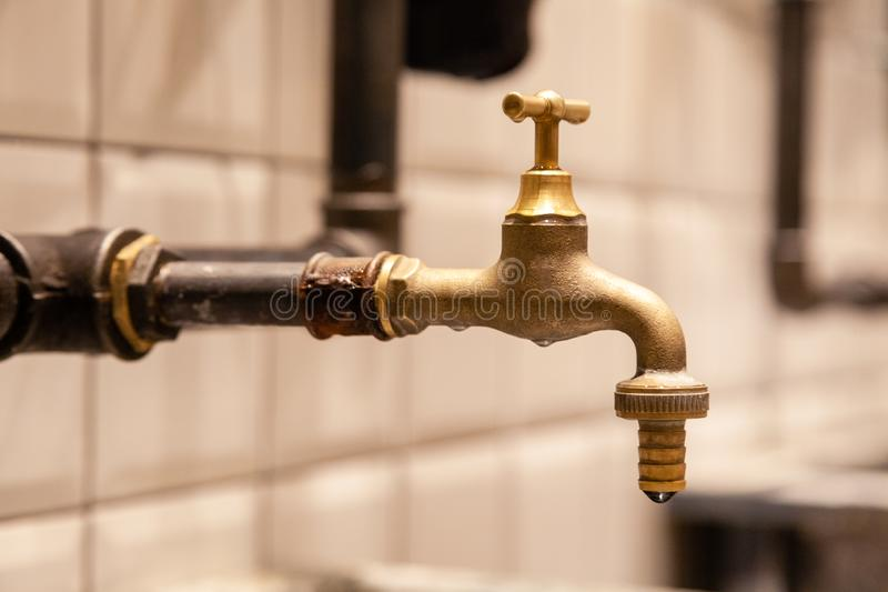 Closeup copper faucet, black industrial pipes on wall with white tiles. Concept designer bathroom in restaraunt, modern interior royalty free stock photo