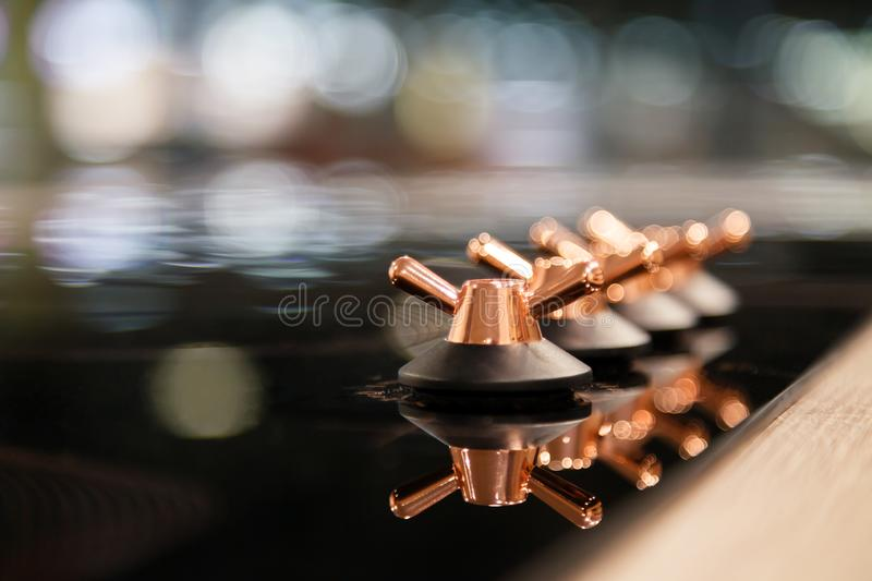 Closeup of the copper knob switch plates are reflected in the black shiny electric or gas hob for the kitchen. Concept modern stock image