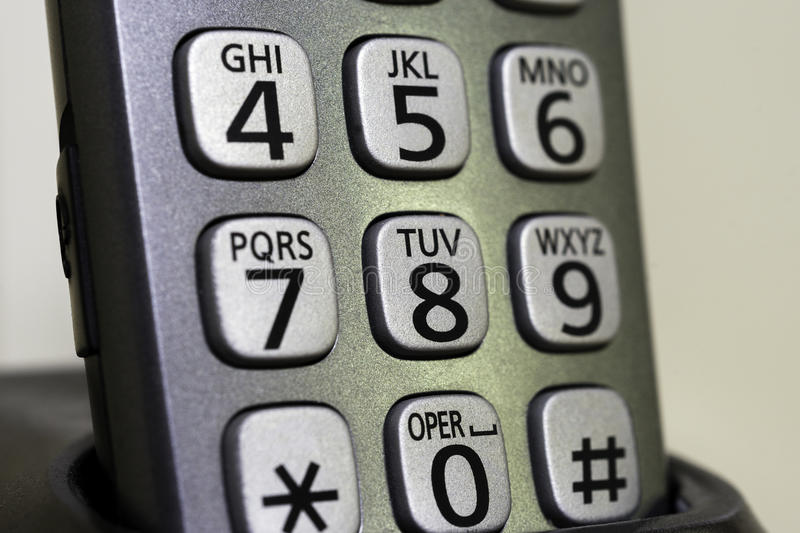 Closeup of cordless phone numbers and letters on buttons sitting. In base cradle charging royalty free stock image