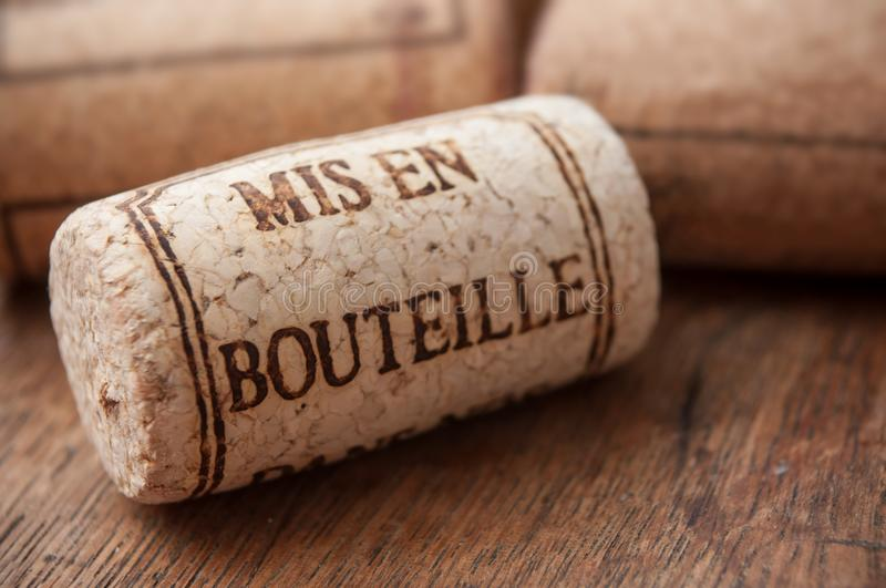 Cork wine stopper with text - bottled on wooden table. Closeup of cork wine stopper with text - bottled on wooden table background traduction text in french stock photography