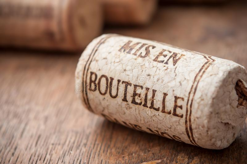 Cork wine stopper with text - bottled on wooden table. Closeup of cork wine stopper with text - bottled on wooden table background traduction text in french stock images